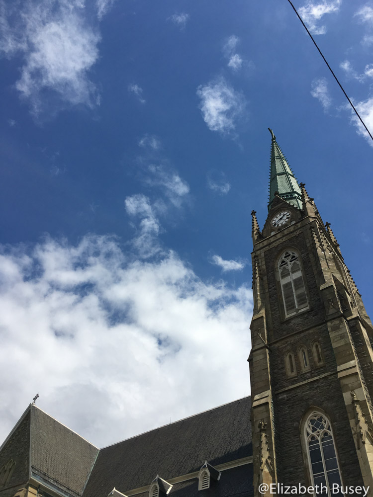 Church spire seems to touch the rapidly moving clouds.