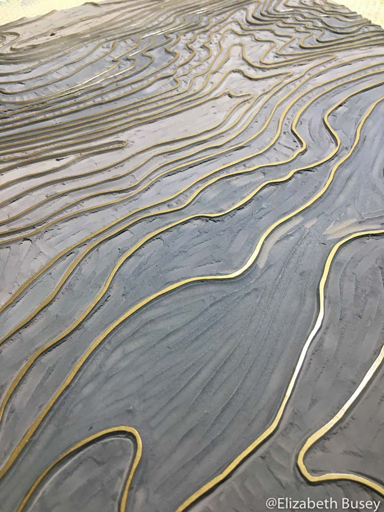 Gold ink on the last layer of the topography linocut.