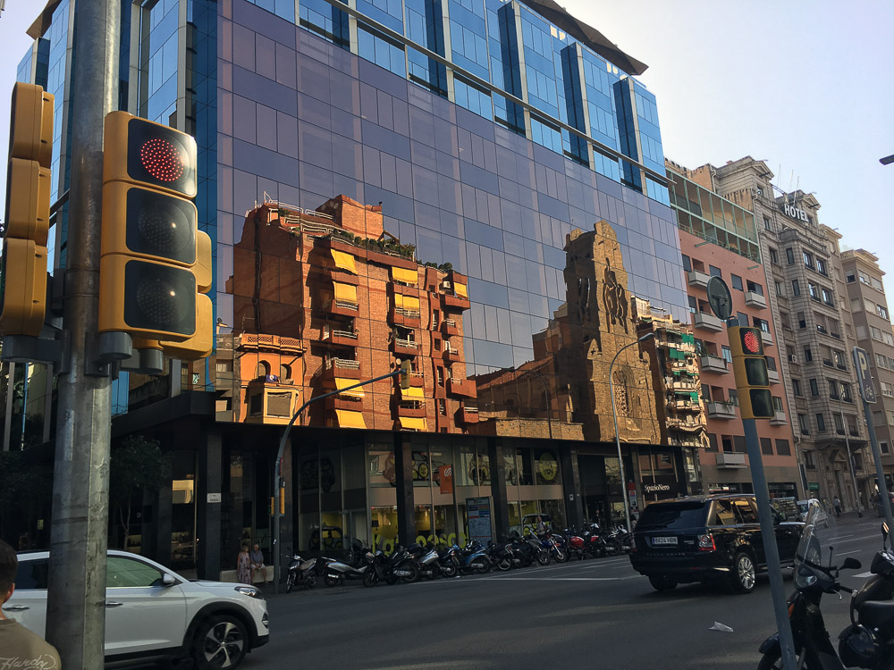 glass building Barcelona Spain reflecting older apartments church hot summer